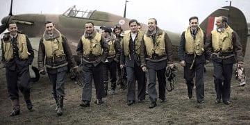 Fot.: Wikimedia Commons/ 1940 Piloci Dywizjonu 303. Od lewej P/O Ferić, F/Lt Kent, F/O Grzeszczak, P/O Radomski, P/O Zumbach, P/O Łukuciewski, F/O Henneberg, Sgt. Rogowski, Sgt. Szaposznikow. Fotografia została pokolorowana. Oryginalna kolorowa fotografia polskich pilotów z czasów Bitwy o Anglię: http://i.iplsc.com/piloci-303-polskiego-dywizjonu-mysliwskiego-przy-samolocie-s/00028AAYH6FKNL2G-C116-F4.jpg
